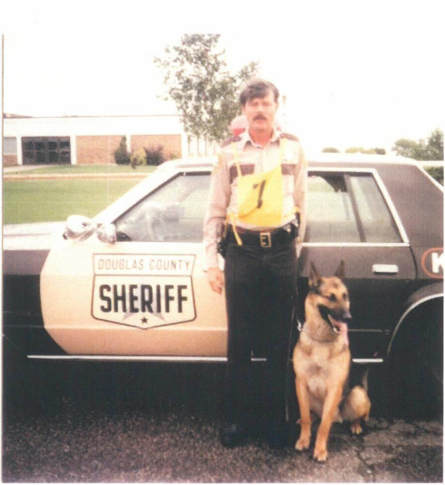 K-9 and partner standing next to their patrol car