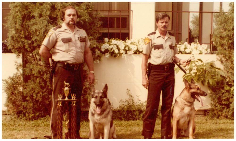 Two officers stand next to their K-9s