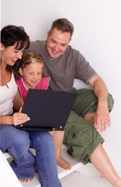 2 adults and 1 child sitting in front of a laptop