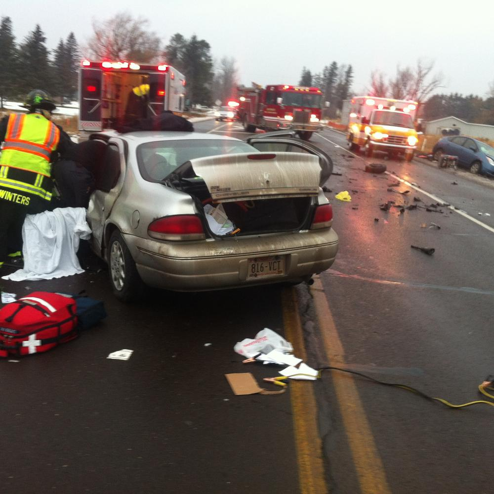 emergency vehicles in the background with crash remnants on the road, vehicle in foreground with trunk and doors open
