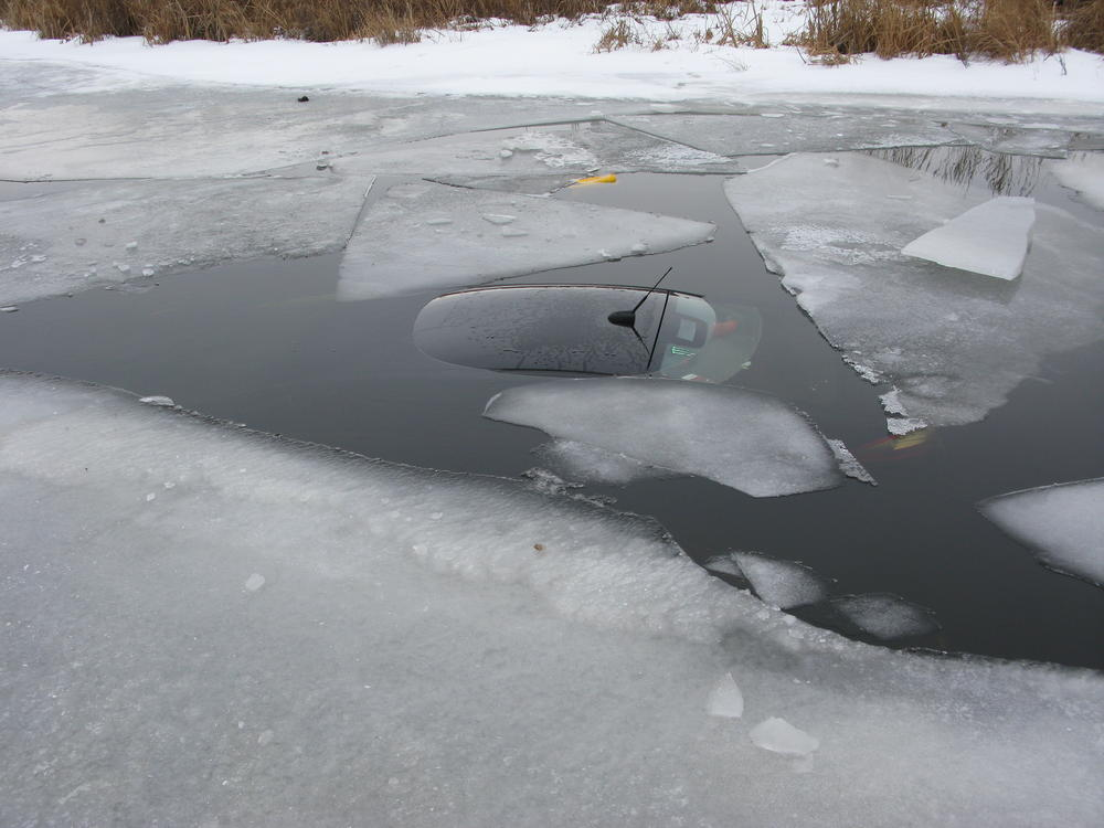 Vehicle submerged in water under ice